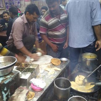 A man rolls dough into a flat circular disk, ready to be thrown into a fryer nearby where puri is being made. Several people crowd around and drool at the delicacies