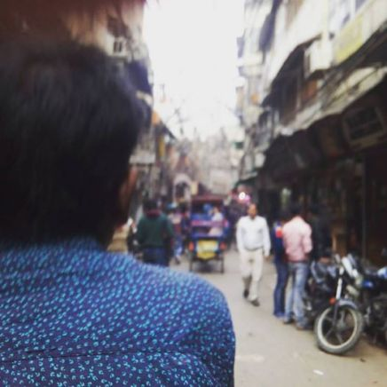 the back of a rickshaw biker can be seen as he pedals the viewer down narrow alleys in New Delhi