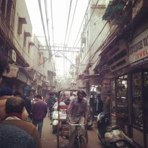 an alley in Old Delhi market, a rickshaw driver is seen pedaling toward the camera, many people walk about.